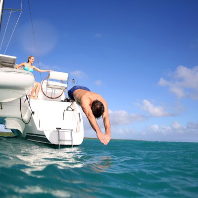 A man jumping from a yacht.