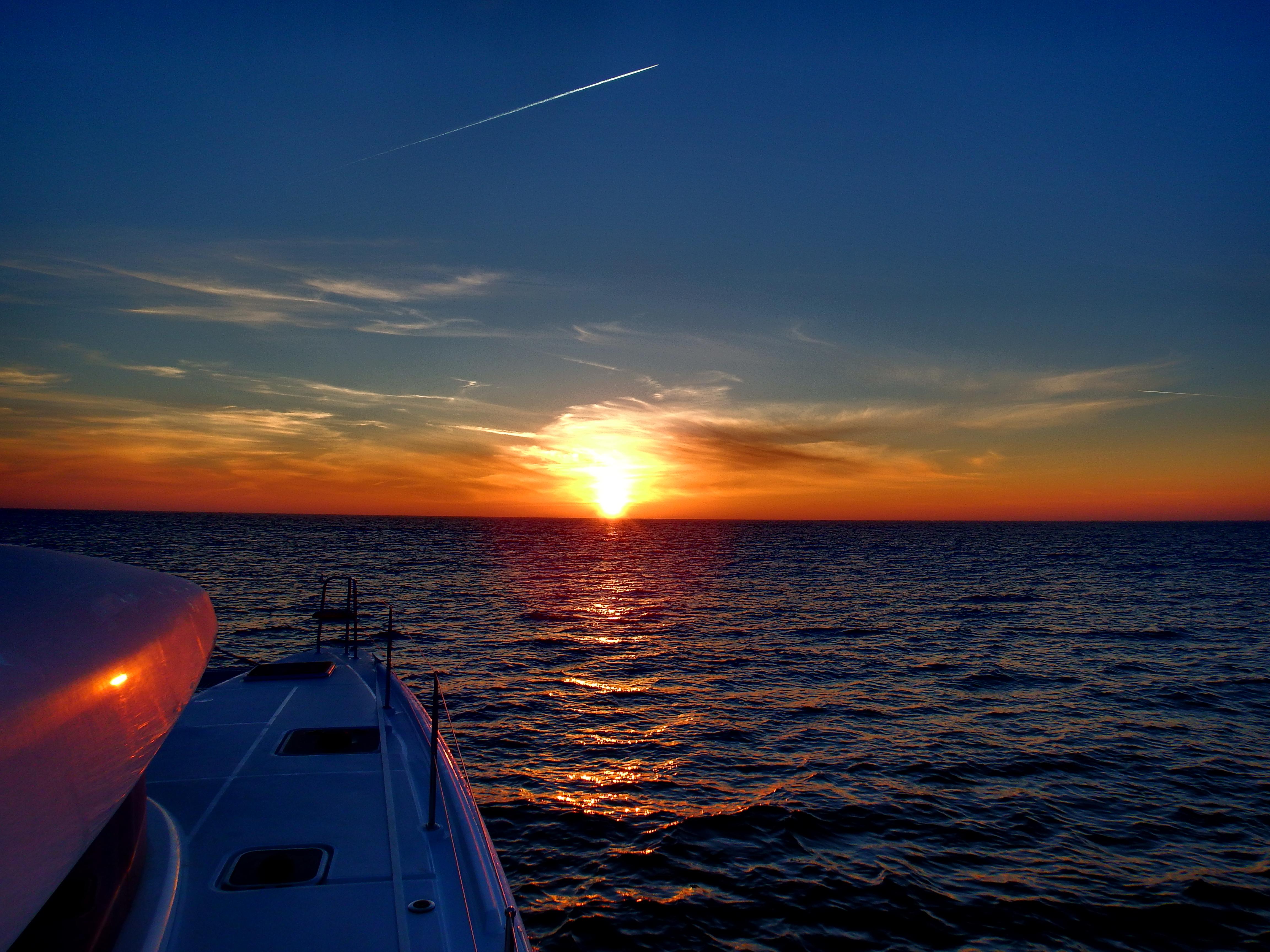 Catamaran sailing into sunset